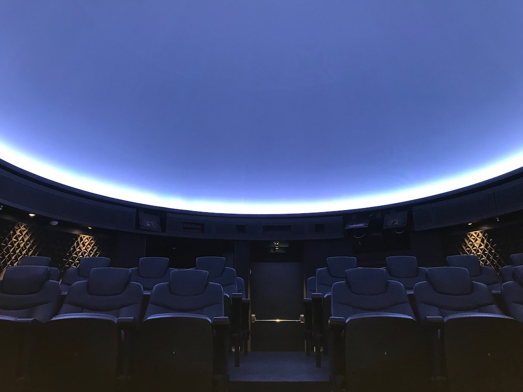 A blank white sky is highlighted by a bright white light outline over chairs in a cruise ship planetarium