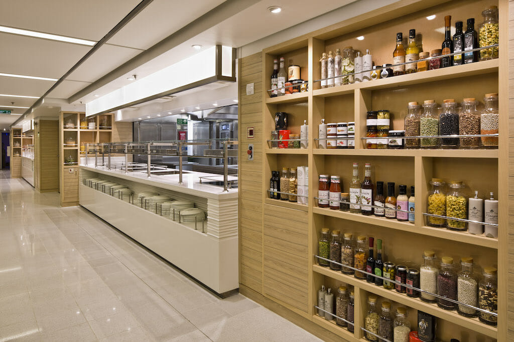 A brightly lit room with shelves filled with spices and food while a cafeteria-like bar awaits customers