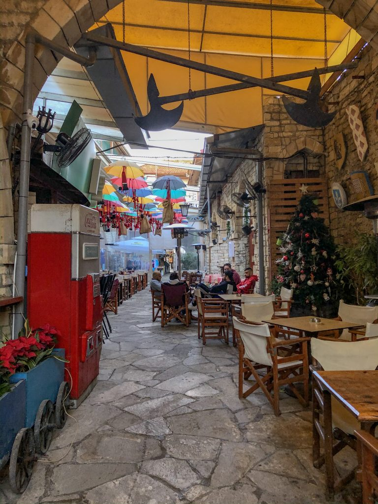 Old narrow street in Limassol with cafes and colorful umbrellas for shade cover
