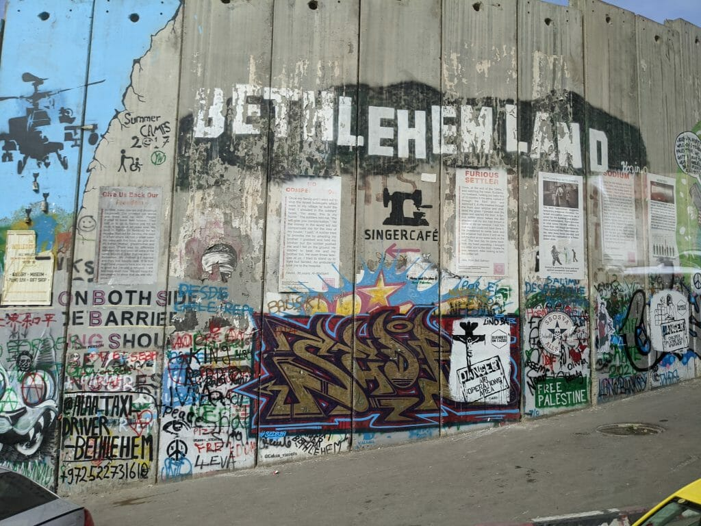 Murial on the Wall between Palestine and Israel with pictures and Headline Bethlehemland