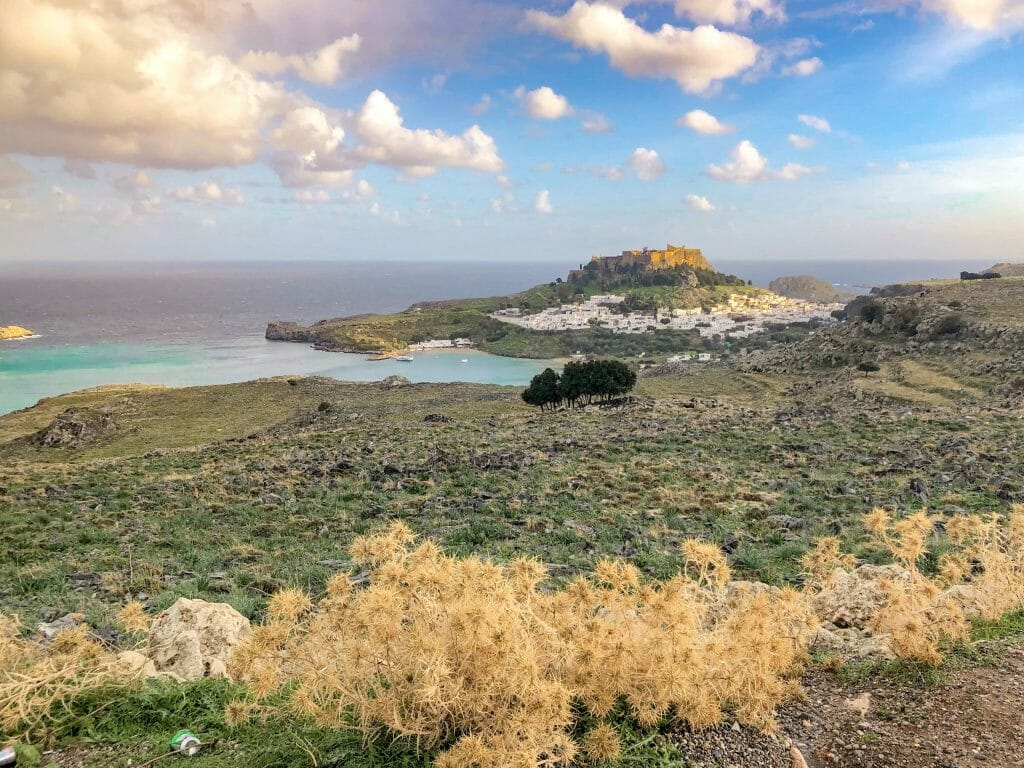 View at Lindos from a distance, with turquoise water to the left and the acropolis sitting on top of the mountain overlooking lindos and the ocean