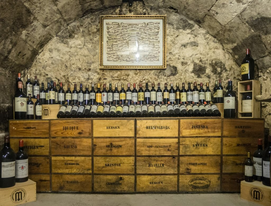 Wood boxes stacked in a vaulted cellar with Burgundy wine bottles on on top