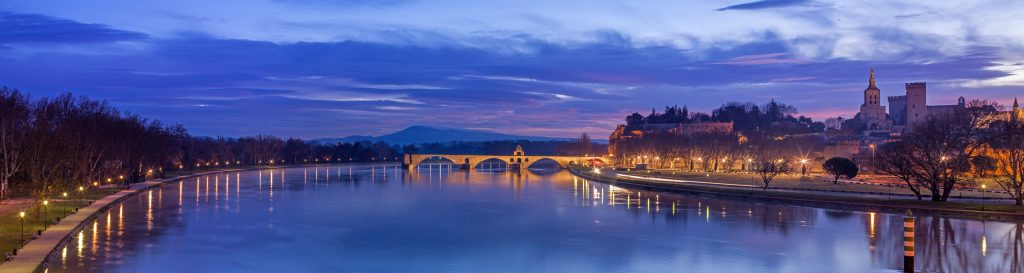 Panorama of Avignon at dusk with purple sky, river and bridge