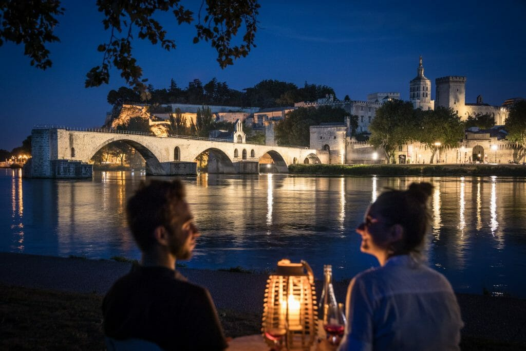 Couple on table with candle light in front of Pont Saint-Bénézet Bridge in Avignon