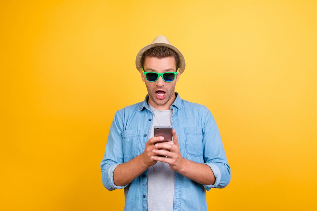 Man with Phone in front of Yellow background