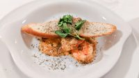 Prawns in tomato sauce on a white plate with a slice of bread and a sprig of parsley on top