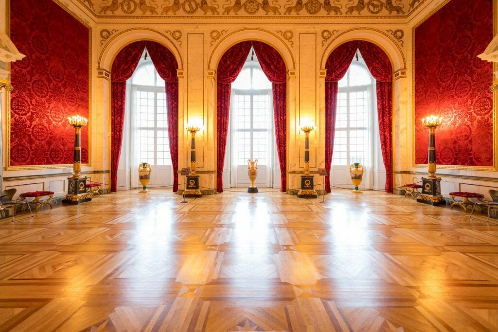 Large ball room with three tall windows with red curtains at the Danish Parliament also known as Christiansborg Palace in Copenhagen Denmark