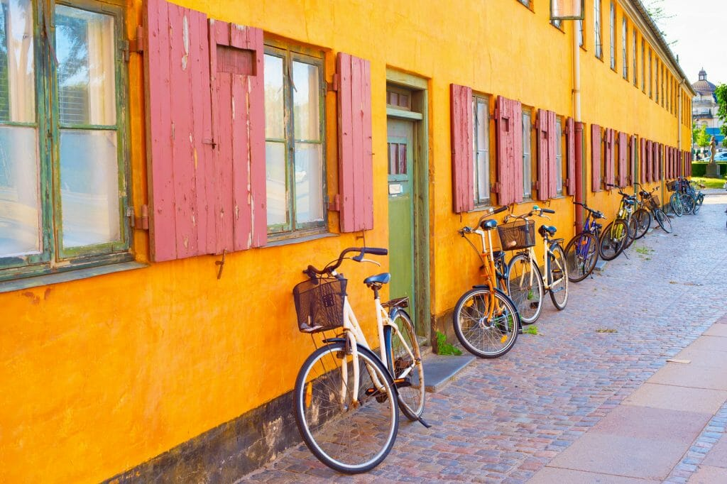 Bicycles leaning on old yellow building in Copenhagen