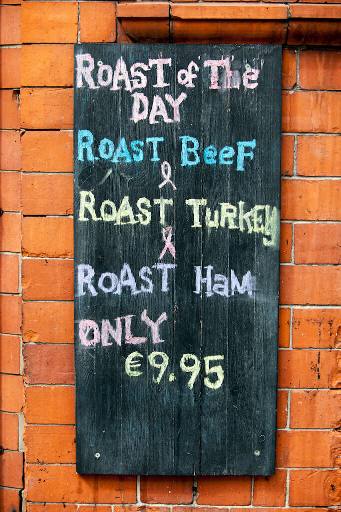 Cafe menu with chalk writing and a black background against a red brick wall in Dublin