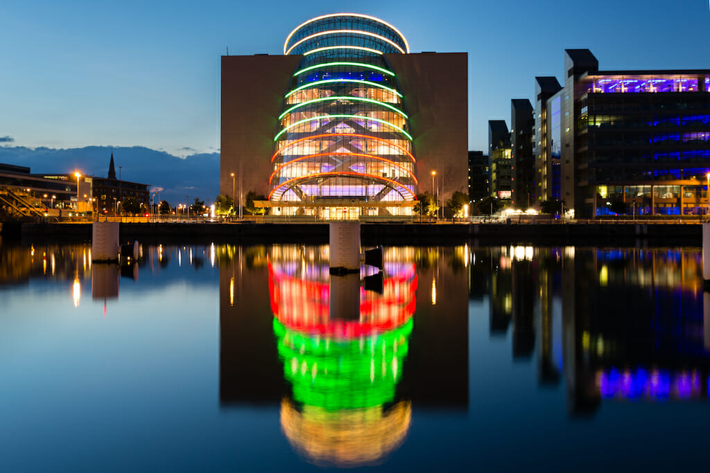 The bright lights on the convention centre in Dublin shine brightly and reflect in the water below, the lights from the other buildings aren't as bright in the early night