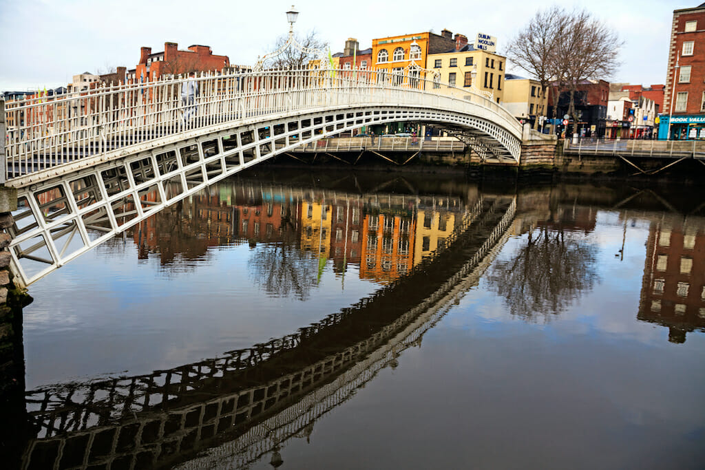 A white bridge goes over reflective water leading to a street lined with colored buildings on a gloomy day