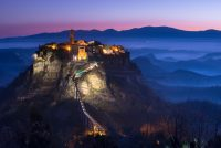 Small Italian Village on top of a hill with a bridge leading up to it. Photographed at dusk with foggy hillside in the background. Civita di Bagnoregio at dusk