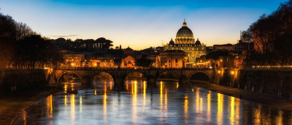 River Tiber with bridges and St Peters Basilica in the background at dusk - Italy Itineraries