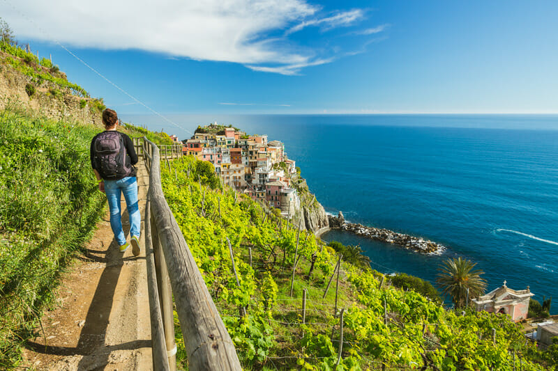 Man hiking on the path in vineyard near Manarola village. Cinque Terre. Liguria, Italy.