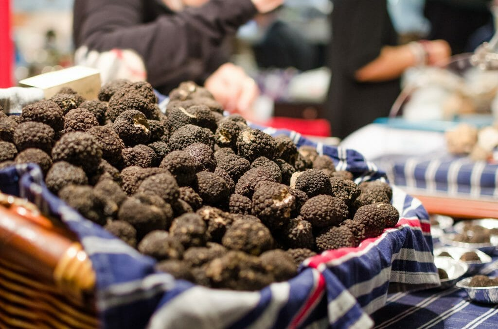 A lot of black truffles in a basket on a market booth