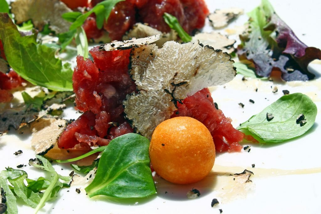 Beef tartare with black truffle on a white dish