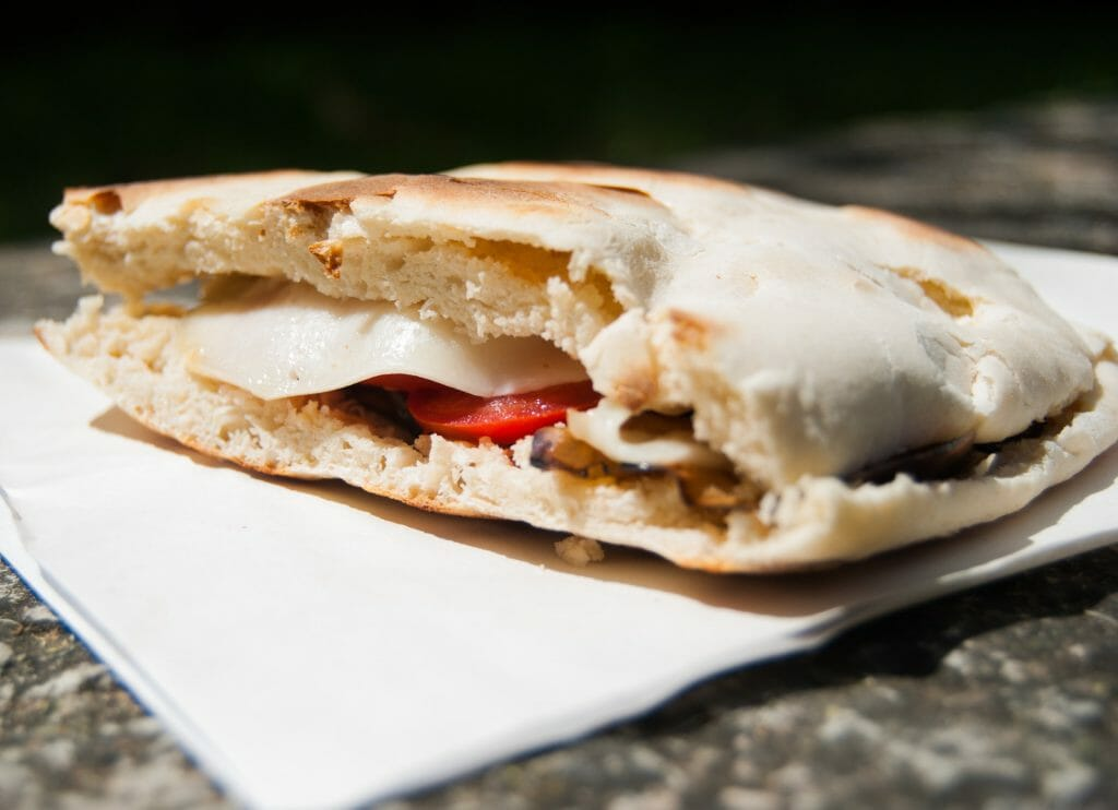 Close-up of vegetarian Crescia typical sandwich of Gubbio Special bread of the center of Italy with cheese tomatoes and aubergine