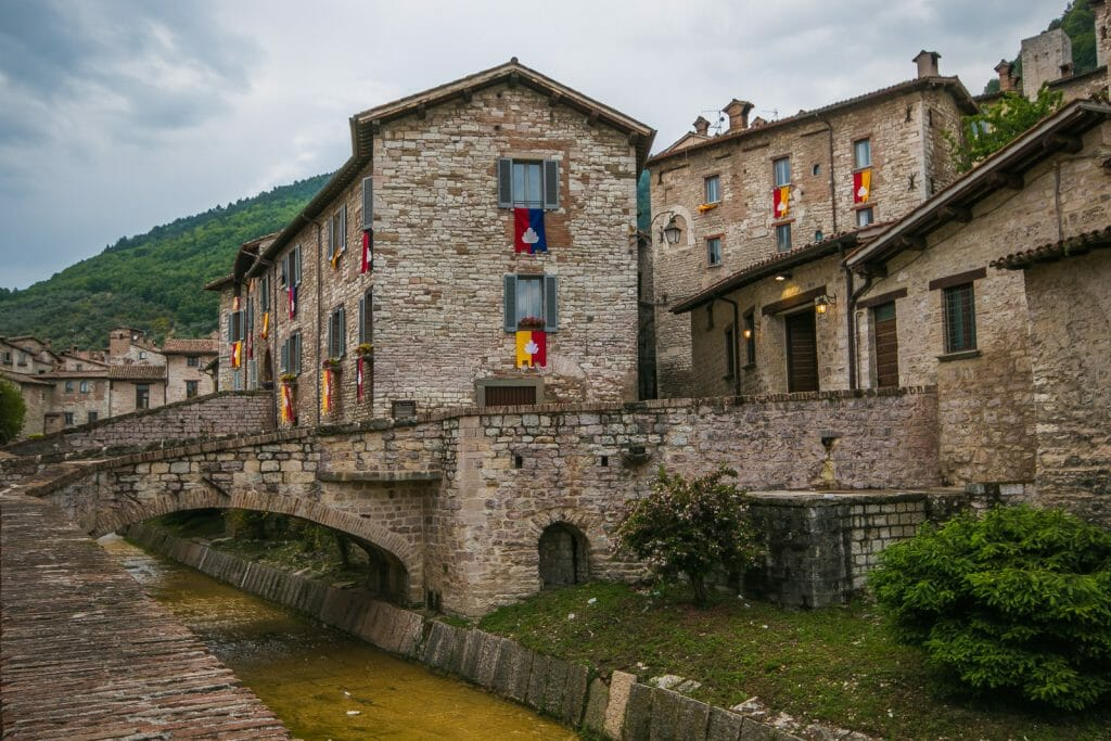 Old stone buildings behind a bridge