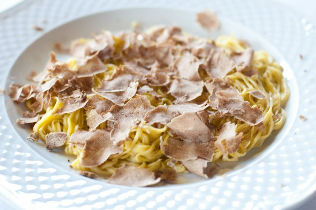 Yellow Tajarin pasta with butter and truffle on a white plate
