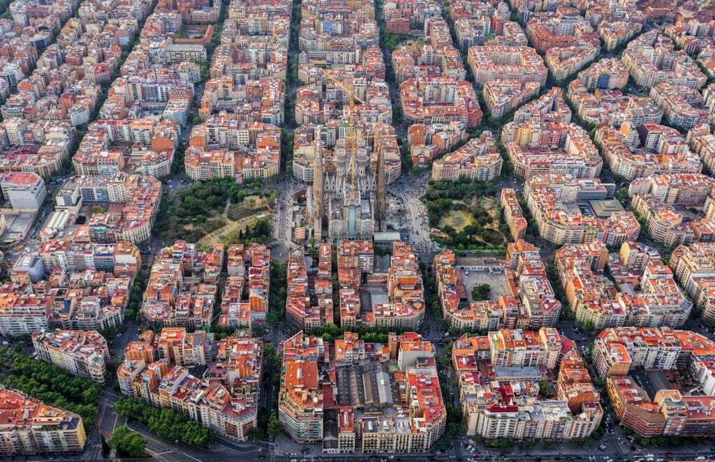 Aerial view of Barcelona Eixample residencial district and Sagrada familia between typical urban grid, Spain. Late afternoon soft light