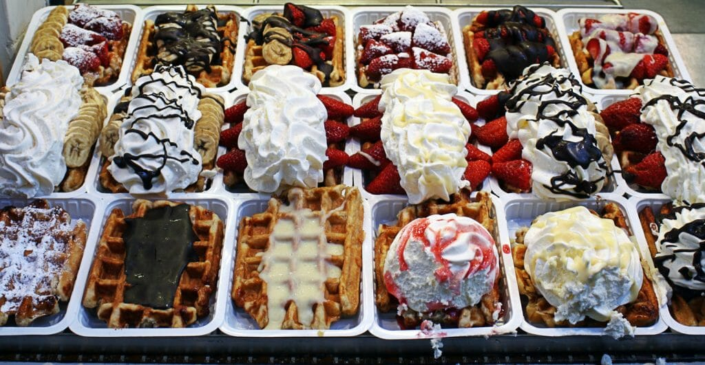 close up view of some brussels waffles with various toppings and sauces