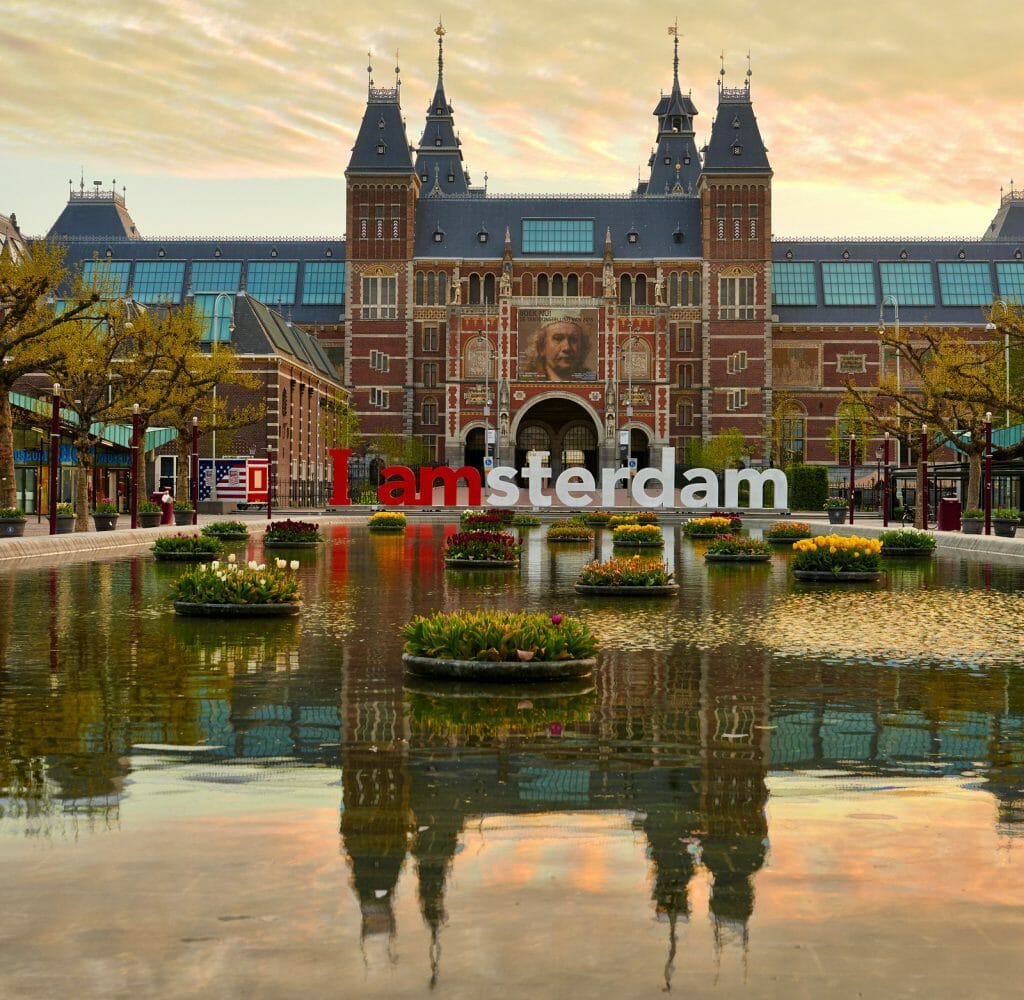 AMSTERDAM, NETHERLANDS: Frontal view of the Rijksmuseum (State Museum) with billboard of Rembrandt with its pond reflection at sunrise in Amsterdam, Holland