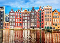 Colorful traditional houses in Amsterdam, reflecting in the canal in front - Amsterdam Itinerary