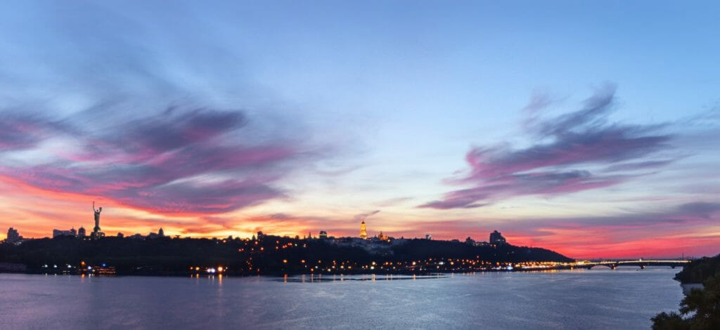 Sunset lit by magical colors, evening cityscape on the skyline of the monastery Lavra and Monument to Motherland. Kiev Multi colored panoramic view with clouds in the sky and reflections in the Dnieper river.