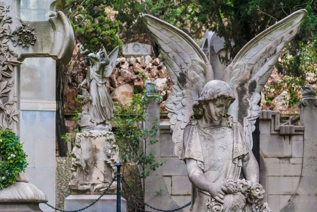 The sculpture of angel on the background of graves and another sculpture on the Montjuic Cemetery, Barcelona, Catalonia, Spain