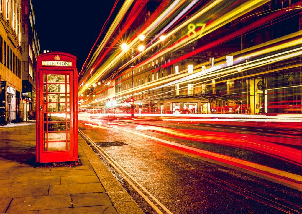 Long exposure photo showing red phone booth in London and light rails of a red double-decker bus passing by on the right