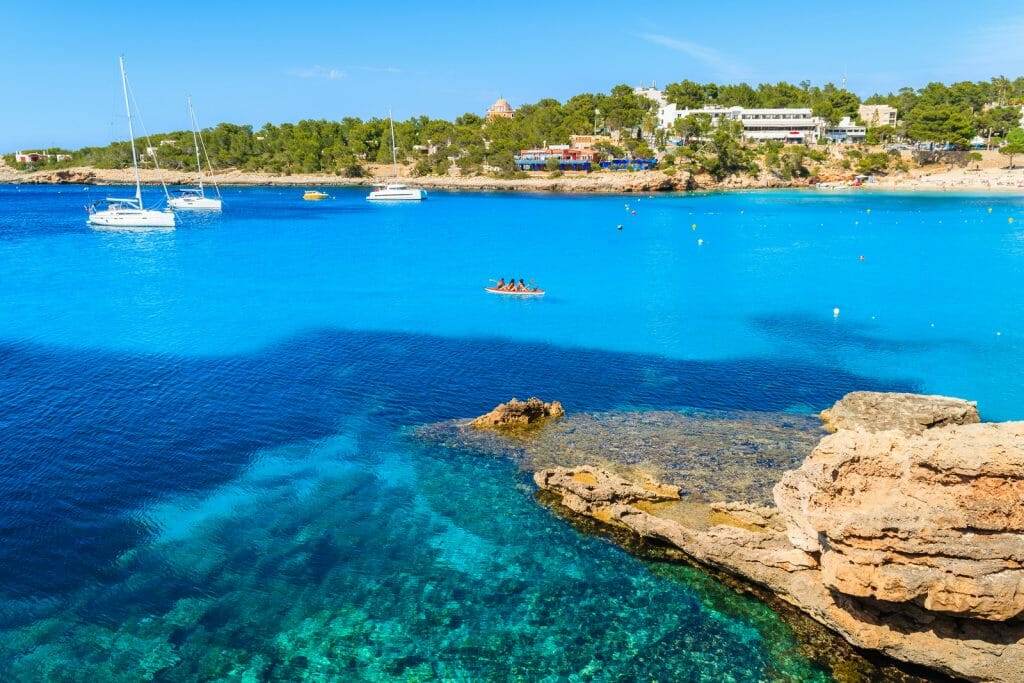 Tourists in kayak paddling on blue sea water of Cala Portinatx bay, Ibiza island, Spain Ibiza is an island in the Mediterranean Sea off the east coast of Spain. It is the third largest of the Balearic Islands.