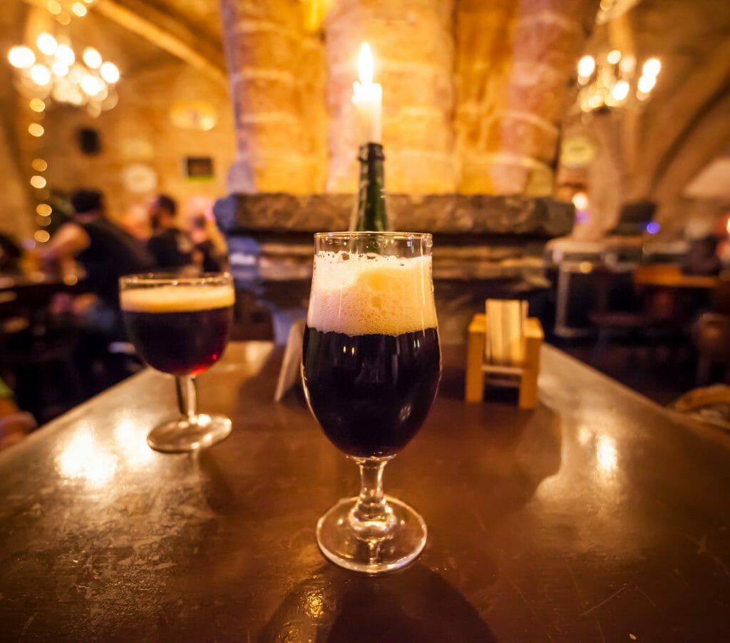 Two glasses of craft beer and a romantic candle in a typical belgian pub