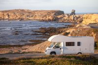 Vacation and travel in caravan.Camper van motor home on seaside road with a sunset - Algarve Camping Tips