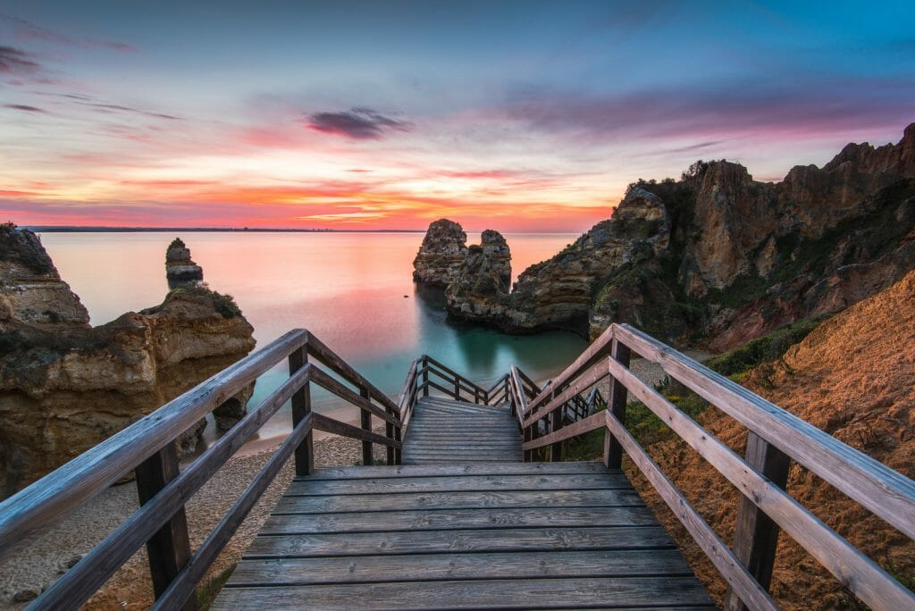 Wooden footbridge walkway to beautiful beach Praia do Camilo on coast of Algarve region, Portugal at sunrise