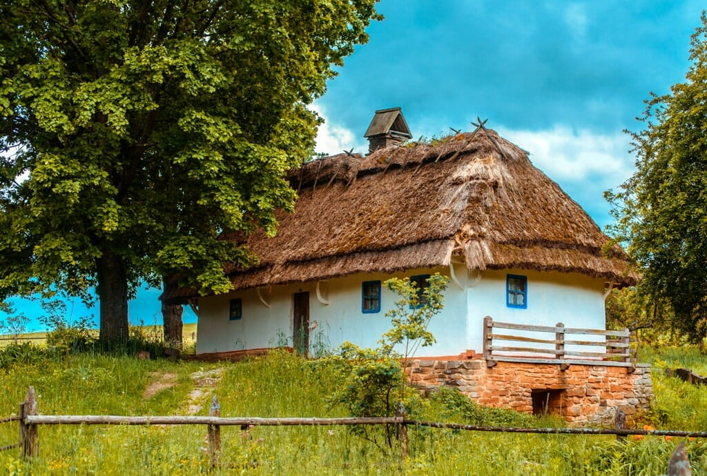 Old white farm house with thatched roof in the Ukrainian countryside