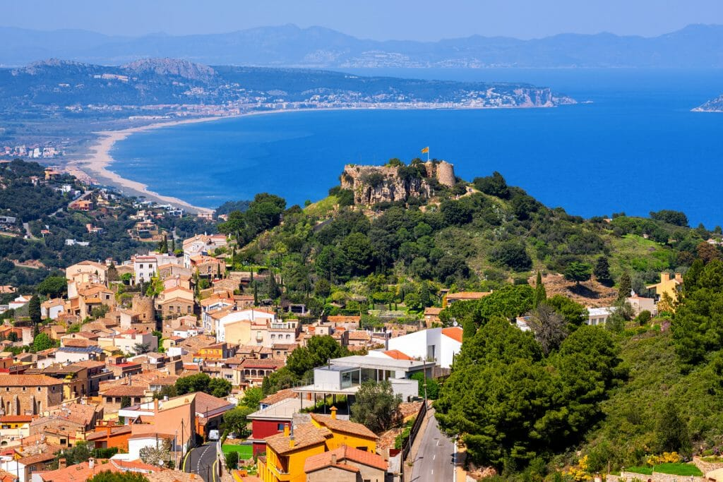 Aerial View of Begur, Old Town and Castle overlooking Mediterranean Sea and the Pyrenees mountains. Begur is a popular resort on Costa Brava, Catalonia, Spain.
