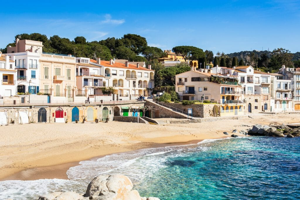 Calella de Palafrugell Beach with white small houses, sandy beach and clear turquoise water, Costa Brava.