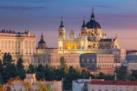 Image of Madrid skyline with Santa Maria la Real de La Almudena Cathedral and the Royal Palace during sunset.