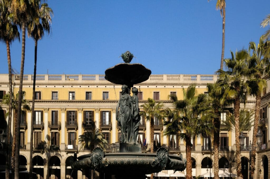 Plaça Reial, metal fountain in front of large yellow building with many columns in the background, square with palm trees, Barcelona, Spain