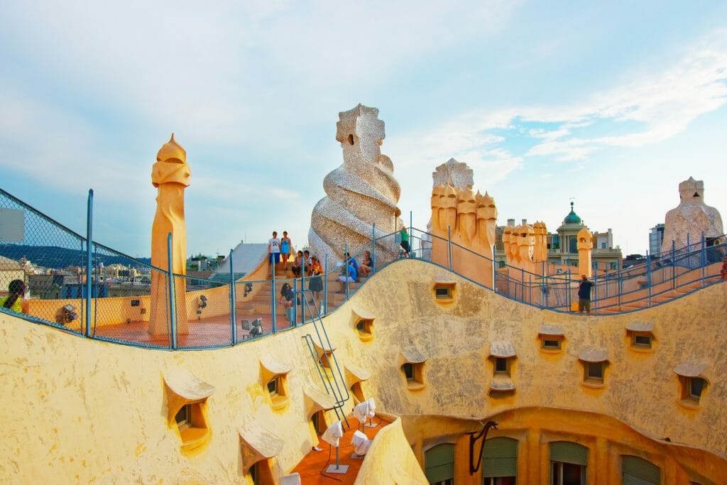 Roof  with chimneys and tourists in Casa Mila building in Barcelona in Spain. Also called as La Pedrera, or Miracle Home, or The Quarry. Designed by Antoni Gaudi