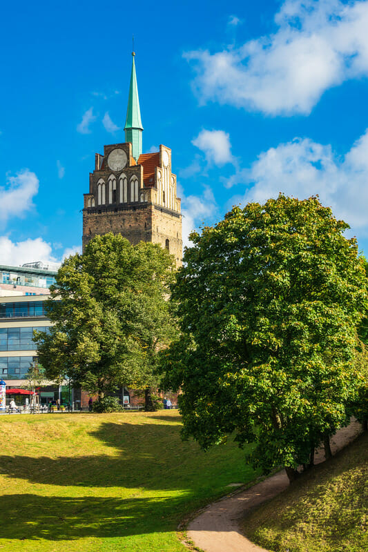 View to a historical tower behind trees in Rostock, Germany.