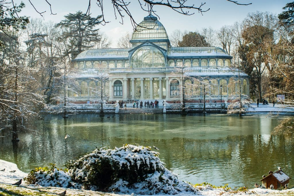 Crystal Palace, a historic glass house in front of a lake in Retiro Park on a snowy day, Madrid Spain