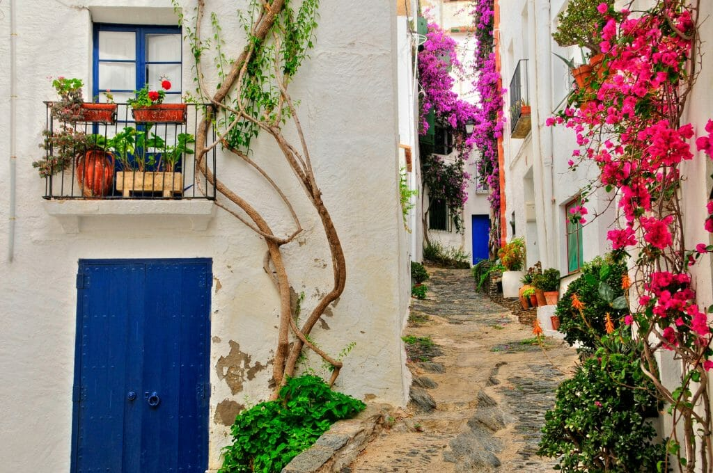View of a street with white houses, blue doors and shutters and pink bougainvillea in Cadaques, Costa Brava, Spain