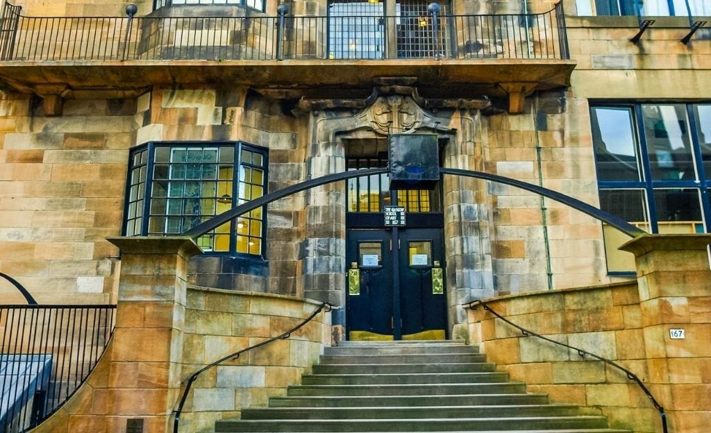 A building designed by Charles Rennie Mackintosh in Glasgow. Yellow and orange sandstone building with a narrowing staircase leading to a decorative black door.