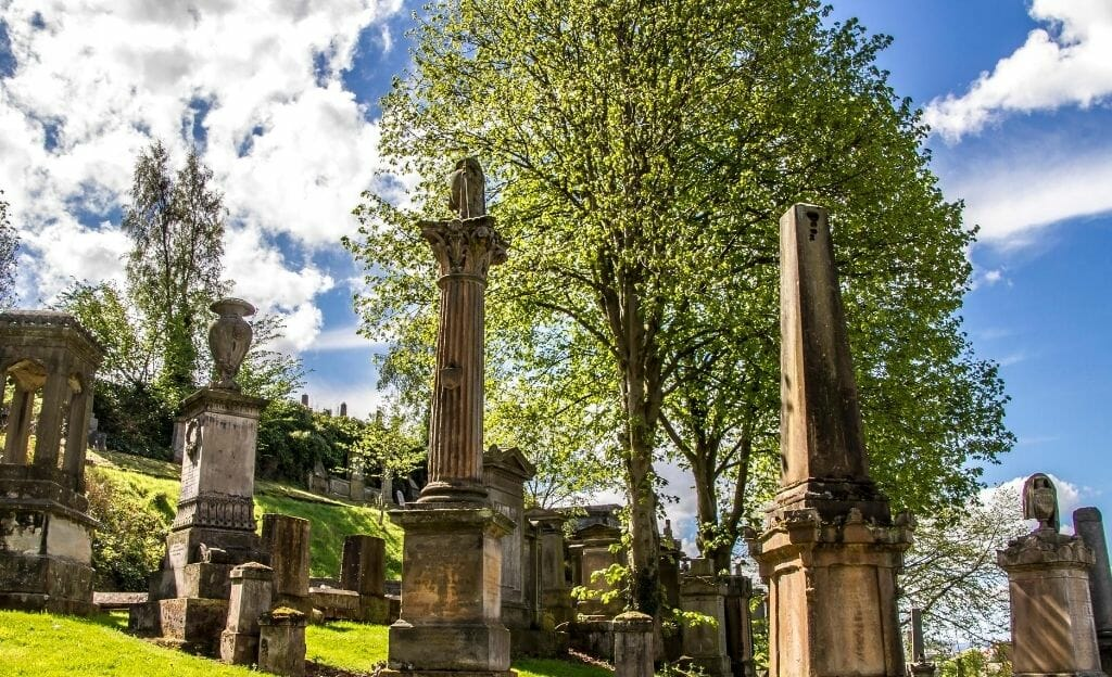 Glasgow Necropolis Cemetery - Tall obelisk-like gravestones in front of a large green treen in the sping time on a sunny day