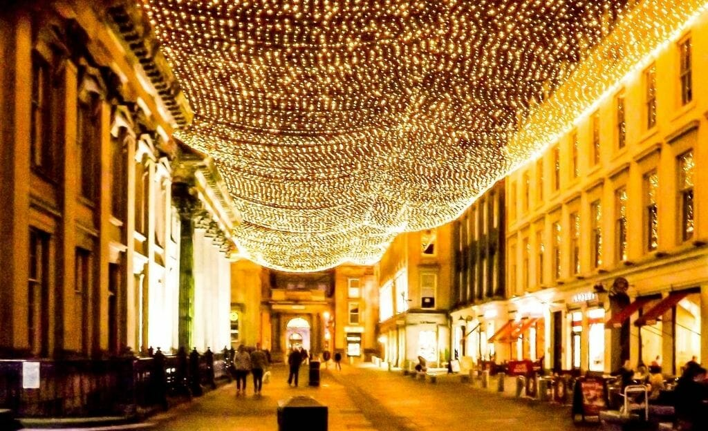 Merchant City Square Glasgow - A square with a lot of restaurants and bars with a net of fairy lights over the street.