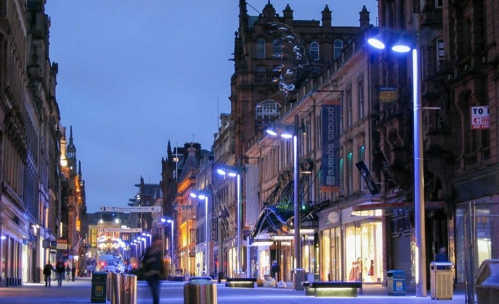 Evening light and blue street light on a shopping street in Glasgow in March. A few unidentifieable people walking