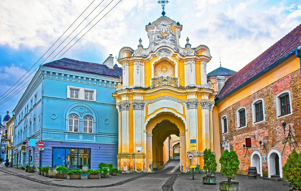 Ornate yellow and white gate house to a monestary next to bright blue and orange building