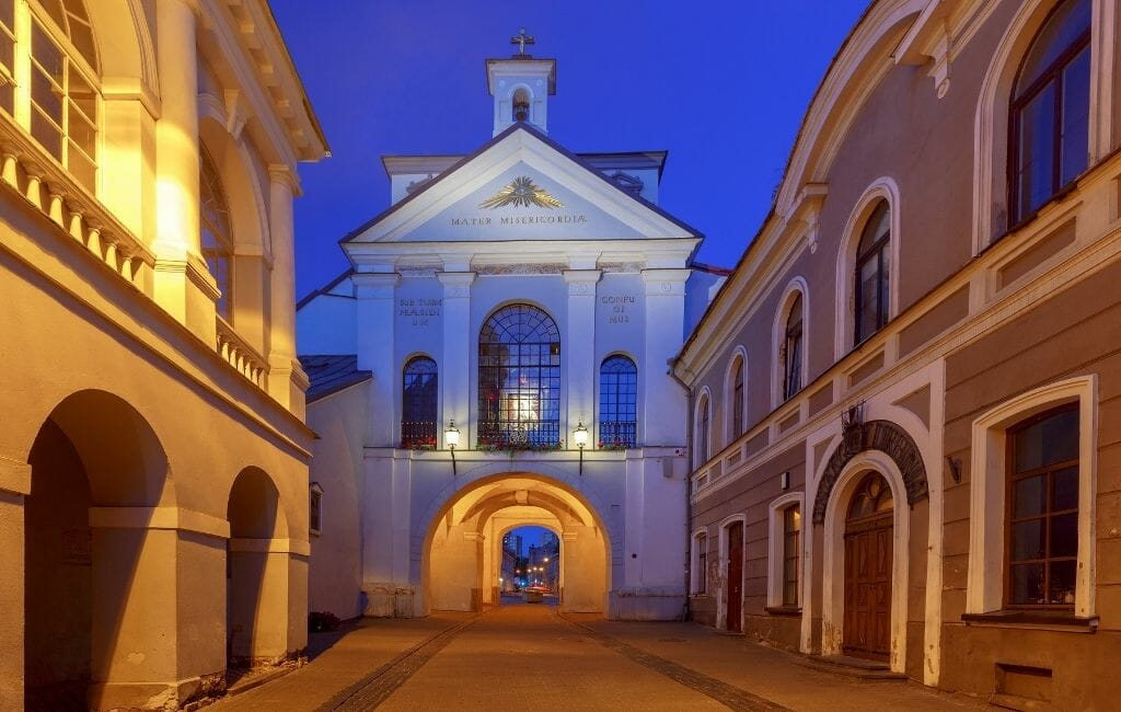 Street leading up to Old city gate of the city wall surrounding Vilnius photographed during blue hour.