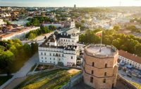 Aerial view of Gediminas Hill and tower during golden hour and Vilnius old town in the background
